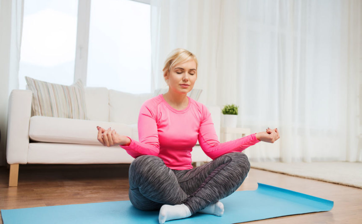 happy woman stretching leg on mat at home