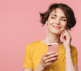 Happy young beautiful woman posing isolated over pink wall background listening music with earphones using mobile phone.