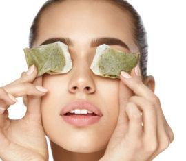 Eye Skin Care. Beautiful Woman With Green Tea Bag Under Eyes